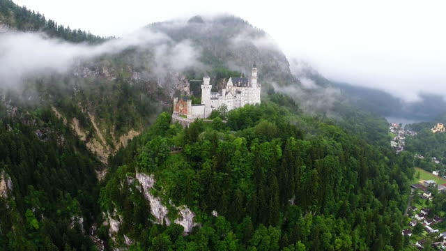 stockvideo's en b-roll-footage met schloss neuschwanstein castle stands in this aerial view in the early morning on june 11 2015 near hohenschwangau germany schloss neuschwanstein... - kasteel