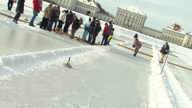 Schloss Nymphenburg, man shot curling stick, some other people, snow, castle in background