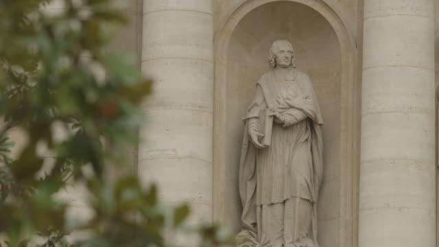 Scholarly statues of Jacques-Bénigne Bossuet and Jean de Gerson adorn the Sorbonne Chapel, a university building, Paris, France.