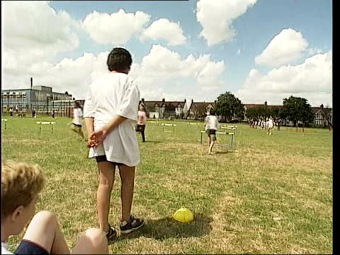 school bans egg and spoon race at sports day lib children competing in relay race children in sack race children watching race - sack race stock videos & royalty-free footage
