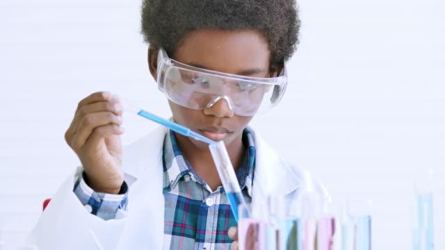 esperimento di biologia scolastica. ragazzo con provetta in primo piano condurre esperimenti scientifici in classe. argomenti dell'istruzione - soluzione video stock e b–roll