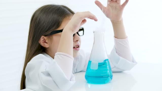 学校の生物学実験。教室でテスト実験カップ科学実験を示す子供。教育トピック。 - 解決策点の映像素材/bロール