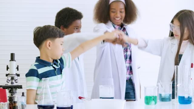 vídeos y material grabado en eventos de stock de experimento de biología escolar. grupo de niños con tubo de ensayo en primer plano llevan a cabo experimentos científicos en el aula. temas de educación - ciencia y tecnología