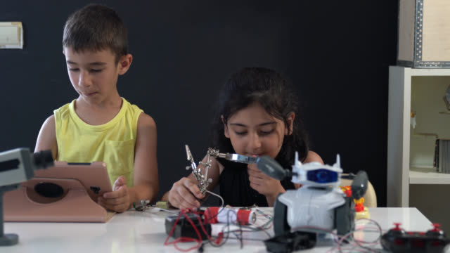 School Boy And School Girl Working On Coding And Robotics