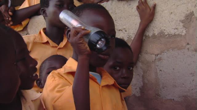 cu school boy holding and shaking torch, tamale, ghana - schulkind nur jungen stock-videos und b-roll-filmmaterial