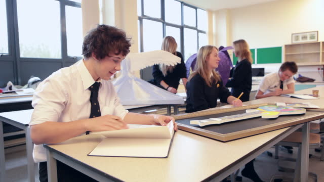 ms school boy looking at sketchbook in art class and rest of class doing art / bristol, united kingdom  - art class stock videos and b-roll footage