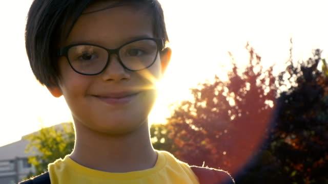 vídeos de stock, filmes e b-roll de menino de escola que levanta na câmera no por do sol - óculos