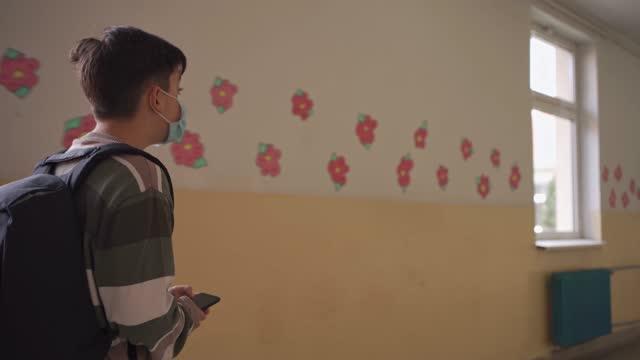 廊下を歩いてクラスロムへ歩く少年 - 少年だけ点の映像素材/bロール