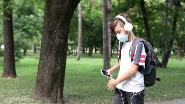 stockvideo's en b-roll-footage met de jongen die van de school beschermend masker in openlucht draagt - hoofdtelefoon