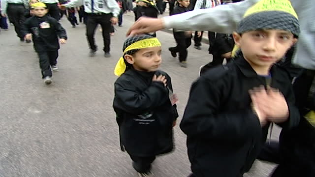 stockvideo's en b-roll-footage met school boys are marching and performing ritual thumping of chest in the ashura procession, organized by hezbollah. ashura commemorates the death of... - hoofdtooi