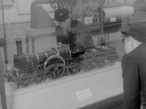 school boys looks at a model of a steam train in a museum. - schoolboy stock videos & royalty-free footage