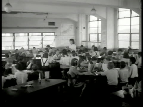 vídeos de stock, filmes e b-roll de school building int ws japanese children in classroom teacher ms japanese boy reading cu school book 'approved by ministry of education' ms female... - guerra do pacífico