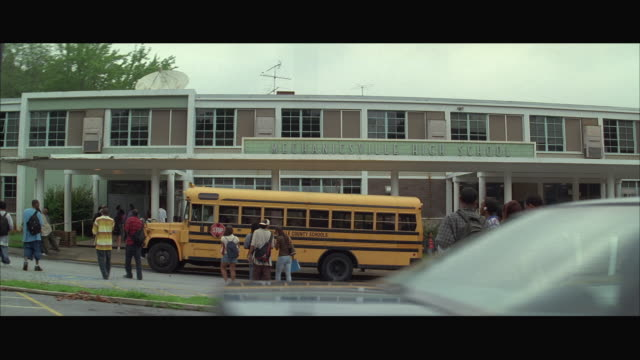 WS ZI School bus and group of teenagers in front of high school / Mechanicsville, Atlanta, Georgia, USA