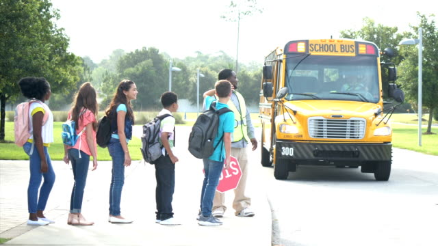 school bus arriving to pick up group of children - 12 13 years stock videos & royalty-free footage