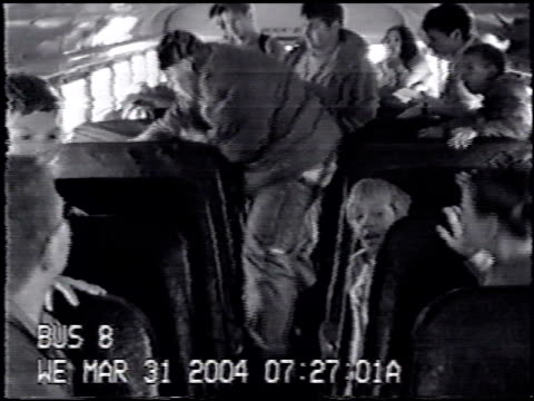 / school bus camera surveillance video kids on bus one large kid walks over to boy sitting in a seat and starts punching him out of nowhere other... - bullying stock videos & royalty-free footage