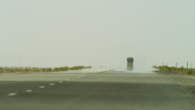 School bus driving along straight desert road in heat haze, UAE
