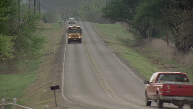 TS School bus driving on country road / United States