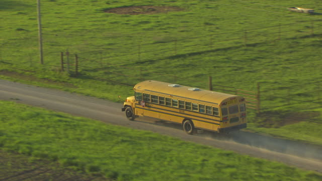 ms aerial zo ts school bus driving on dusty side road in linn county / kansas, united states - tracking shot stock videos & royalty-free footage