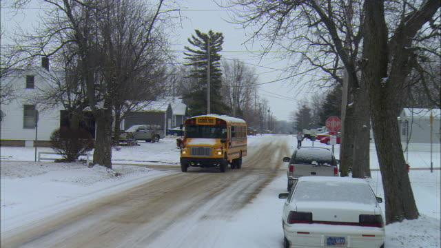 MS PAN School bus driving on snowy street in residential neighborhood, Elkhart, Indiana, USA
