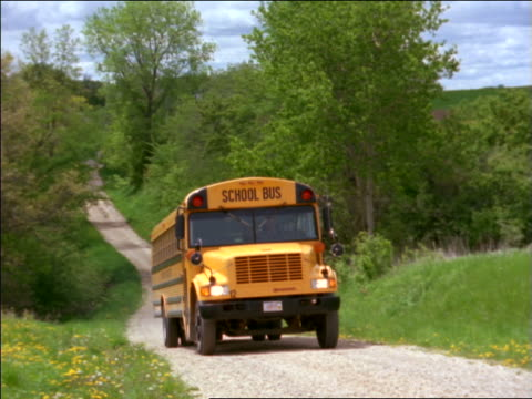 school bus driving past camera on country road - anno 1999 video stock e b–roll