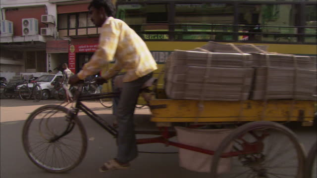 vidéos et rushes de a school bus shares a road with rickshaws in a commercial district in india. - pousse pousse