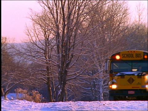 School bus stops and children get on in winter / dog