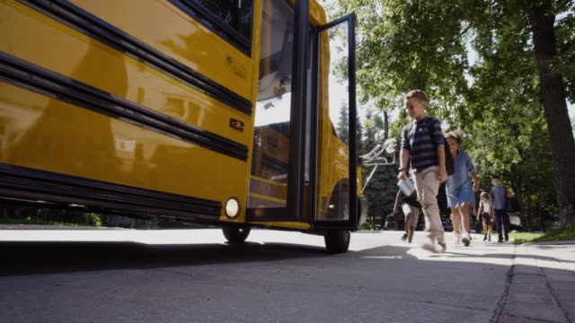 school bus student getting in 4k 4:2:2 slow motion - elementary school stock videos & royalty-free footage