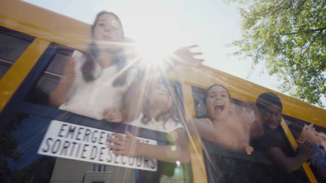 Autobus scolaire Windows étudiants agitant 4K 4:2:2 Slow motion