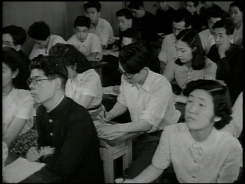 school campus buildings students int vs young adult japanese students in classroom both male female students teacher talking occupied japan... - 戦後点の映像素材/bロール