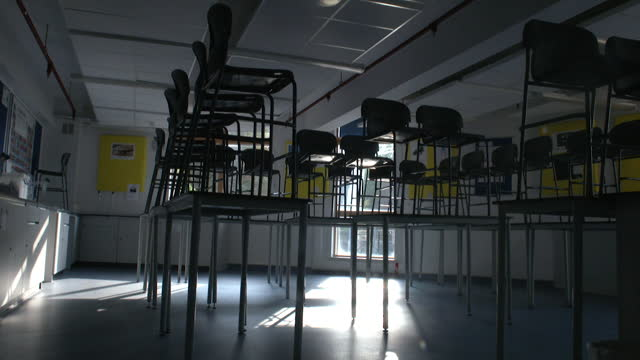 school chairs on desks in empty classroom as some schools in england close early ahead of christmas due to the coronavirus pandemic - furniture stock videos & royalty-free footage