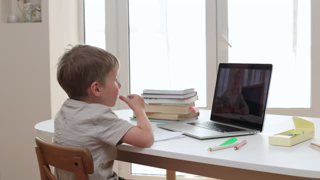 school child doing homework on computer during coronavirus, covid-19 outbreak quarantine. self isolation. seven years old son e-learning with laptop at home. - preschool stock videos & royalty-free footage