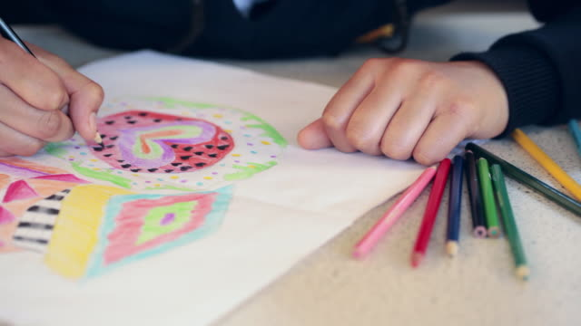 cu pan school child using colour pencils for colouring picture in classroom / bristol, united kingdom  - grundschüler stock-videos und b-roll-filmmaterial