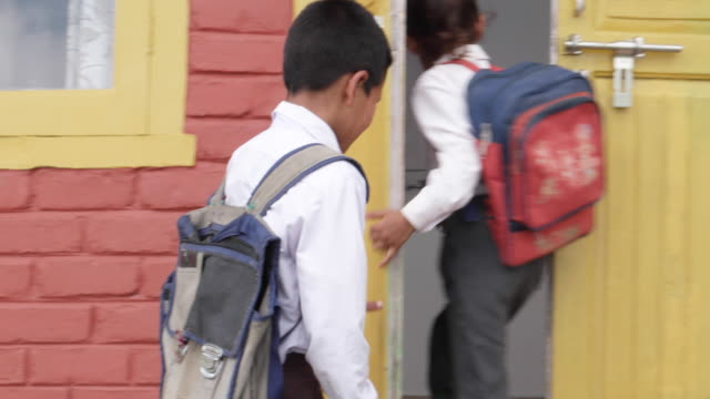 School children arriving home after school in their school uniforms and bags. camera panning follows them