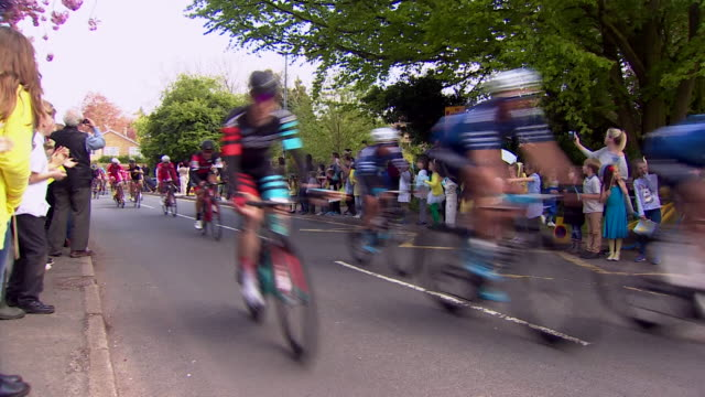 school children cheering cyclists in the tour de yorkshire as they ride past - cycling event stock videos & royalty-free footage