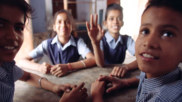 school children classmates friends,  male and female, seated in an empty classroom as they talk discuss work inside a classroom sitting on a bench and resting hands on table for a free period schedule time-table - primary school child stock videos & royalty-free footage