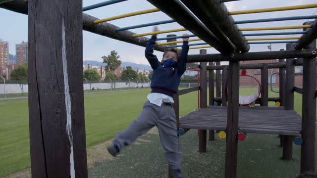 school children enjoying their free time on the monkey bars at school wearing their protective face masks - safety stock videos & royalty-free footage