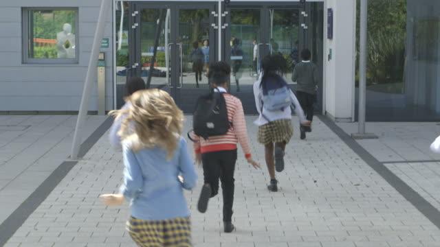 vidéos et rushes de school children entering in school - arrivée