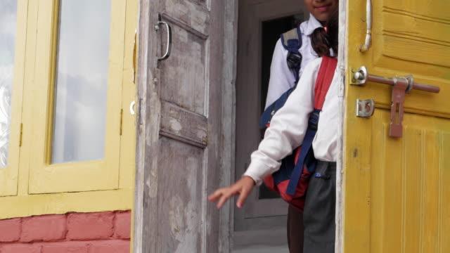 school children exiting the front door of their house for school, pan right - 立ち去る点の映像素材/bロール