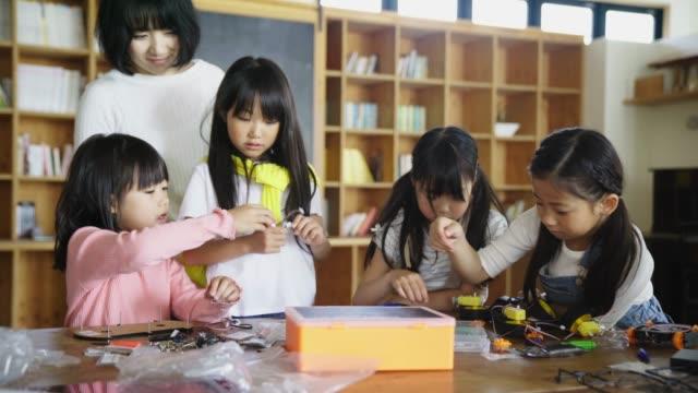 ロボット エンジニア リング レッスンで楽しい学校の子供たち