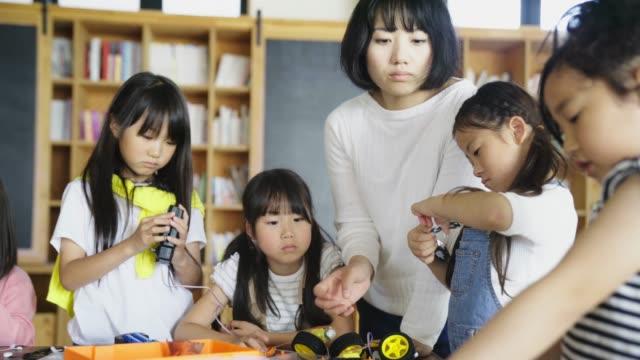 ロボット エンジニア リング レッスンで楽しい学校の子供たち - 教師点の映像素材/bロール