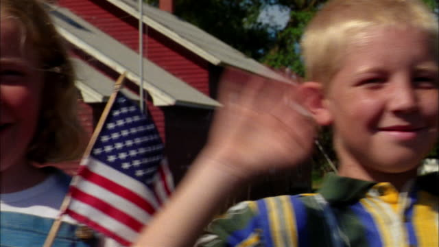 School children hold American flags and wave.