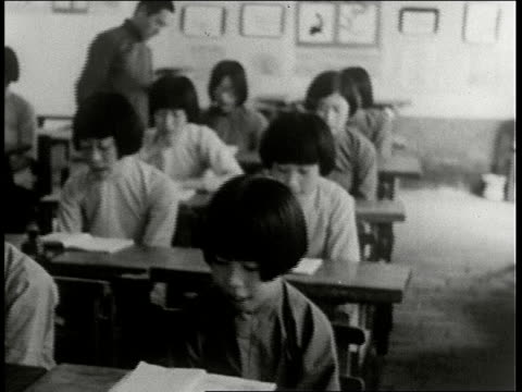 school children in elementary school sit at desks and read and do needlepoint / manchuria - manchuria stock videos & royalty-free footage