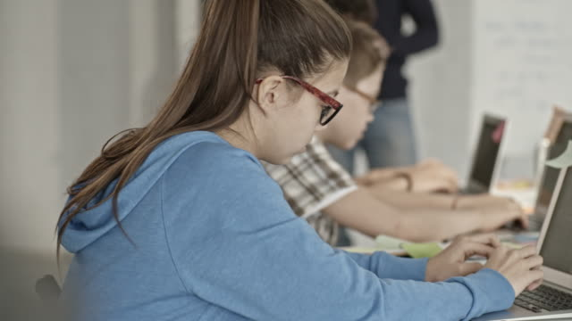 School children in glasses typing on laptops in classroom