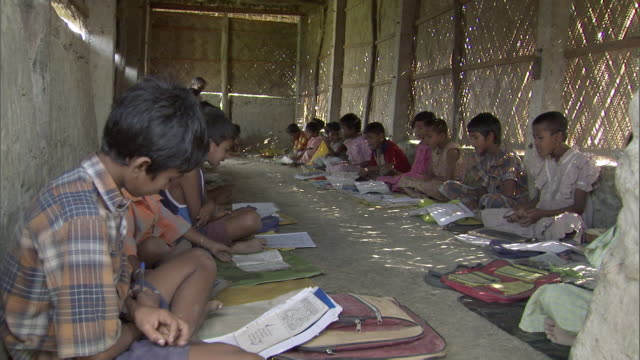 vídeos y material grabado en eventos de stock de ms school children in oneroom school hut sitting  ground and recite their lessons  / india  - libro de texto