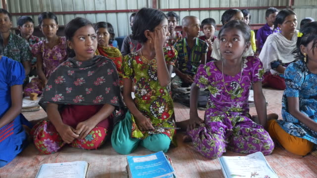 vídeos de stock, filmes e b-roll de school children in rural bangladesh learn and recite english with teaching material provided by a healthcare ngo - bangladesh