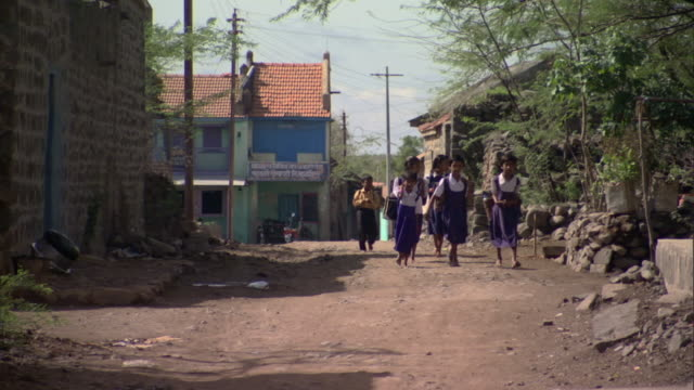 WS PAN School children in uniforms walking in poor village, Pune, Maharashtra, India