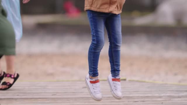 vídeos y material grabado en eventos de stock de slo mo school children jump on wood platform at playground - escuela preescolar