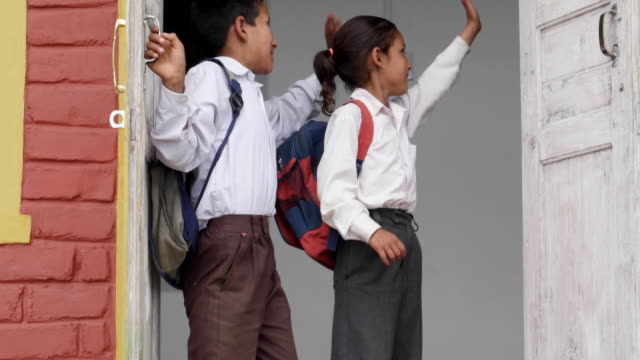 School children leaving home for school in their school uniforms and bags. camera follows them