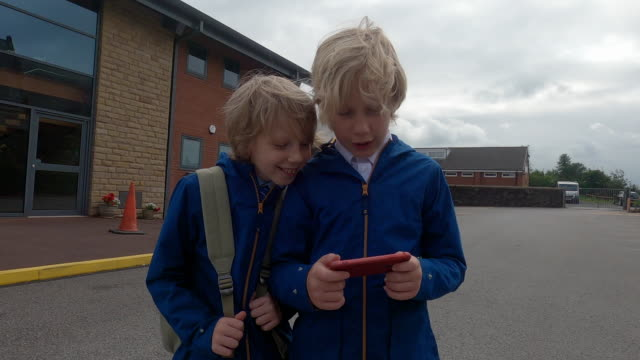school children looking at a phone together - cell stock videos & royalty-free footage