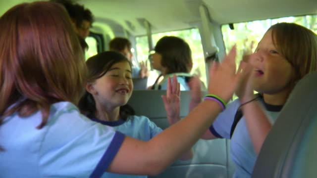 MS, school children (8-11) messing around sitting in van, Bovina, New York State, USA
